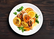 Grilled chicken breast with orange sauce on wooden background, top view